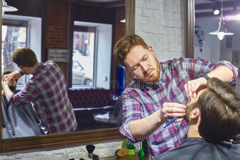 Att raka med en rak rakkniv i barberaren shoppar royaltyfria bilder