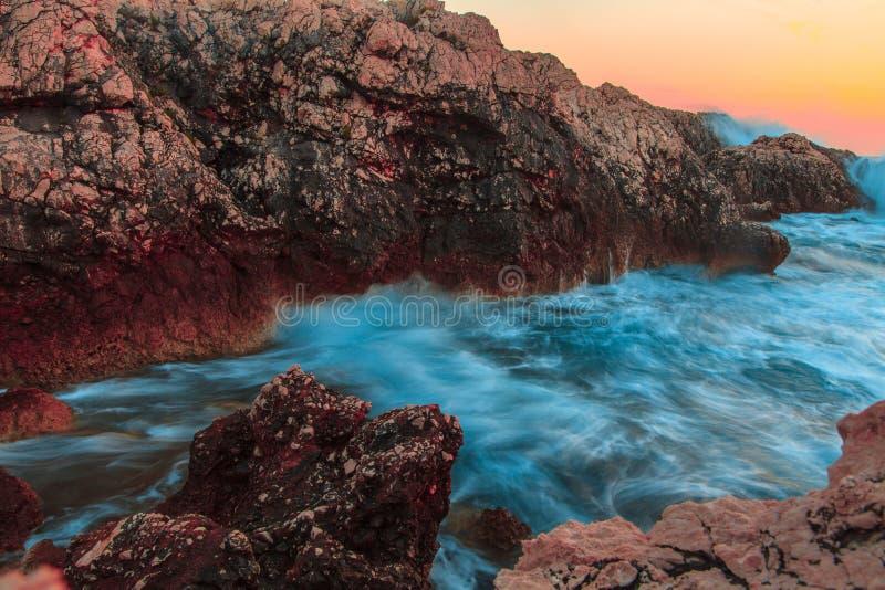Att rasa havvågor som bryter på, vaggar på solnedgången arkivbilder