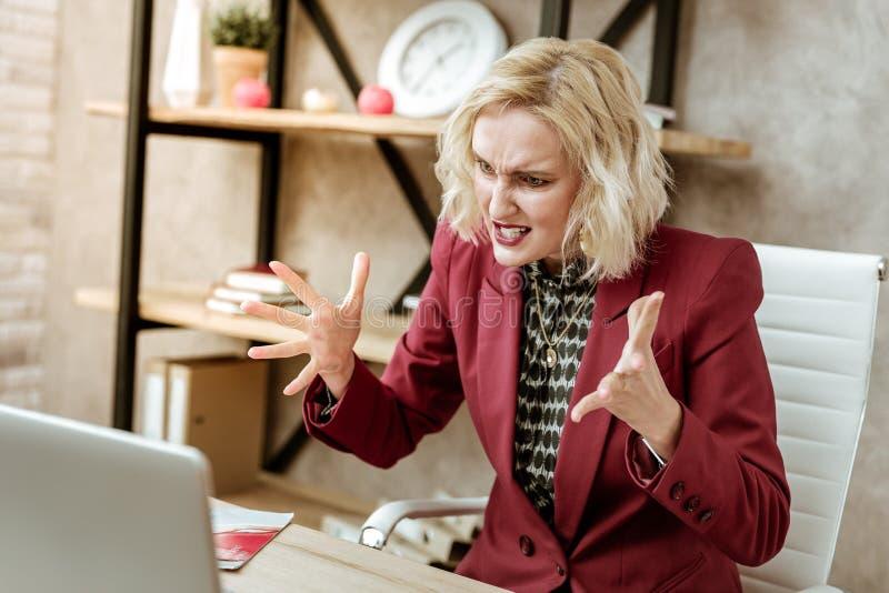 Att rasa startade den blonda kvinnan som talar på höga signaler med affärspartnern arkivbild