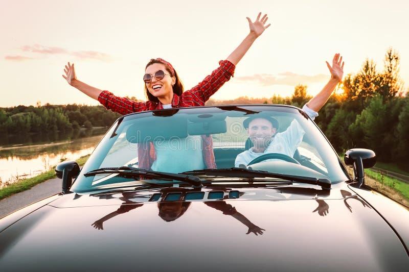 Att resa vid förälskade bil- lyckliga par passerar cabrioletbilen i s royaltyfria bilder