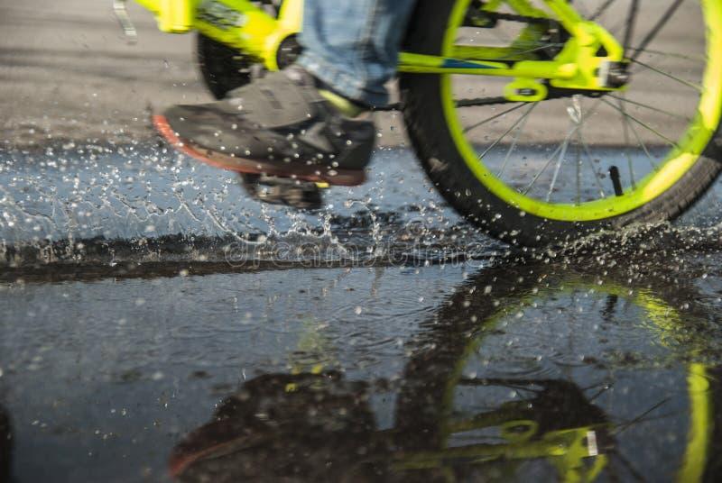 Att rida cykeln över pölarna är så roligt royaltyfri bild