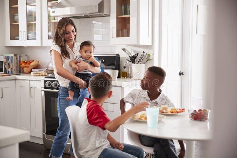 Att rymma för moder behandla som ett barn ställningar i köket som talar med hennes son och hans vän, över för en playdate royaltyfri foto
