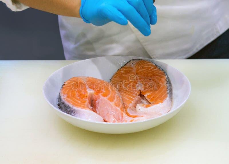 Att sätta för kock saltar på laxskivan som kantjusteras av händer som lagar mat laxfisken arkivfoton