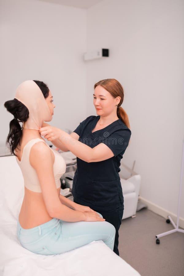 Att sätta för sjuksköterska förbinder på framsida av klienten efter kirurgisk korrigering arkivbild