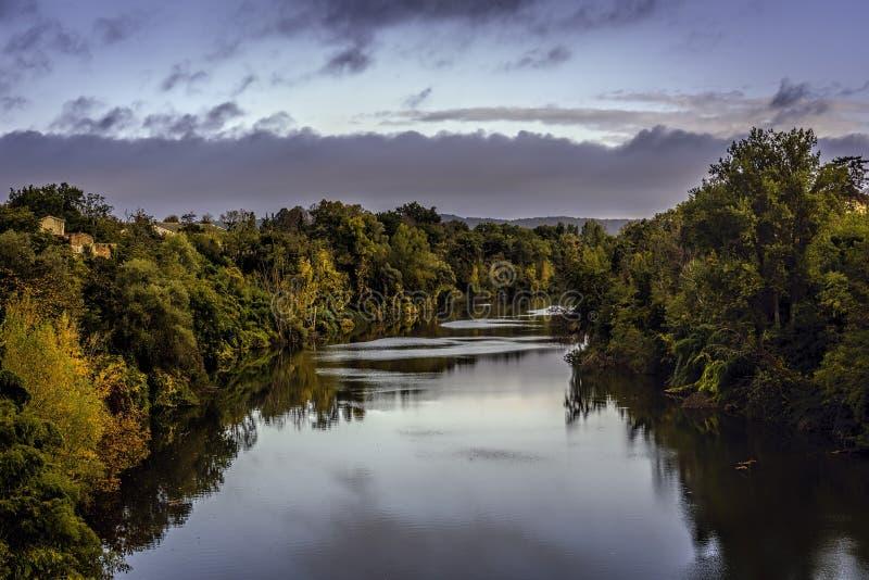 Att se över den Tarn floden i Lisle-sur-Tarn under spridd wirh för blåa himlar fördunklar arkivfoton