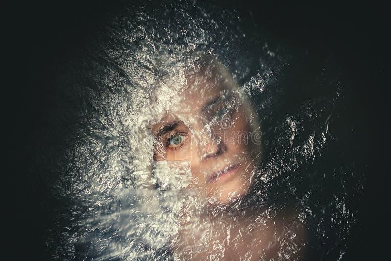 Att se för kvinna skrämde till och med hålet i genomskinlig plast- gardin royaltyfria foton