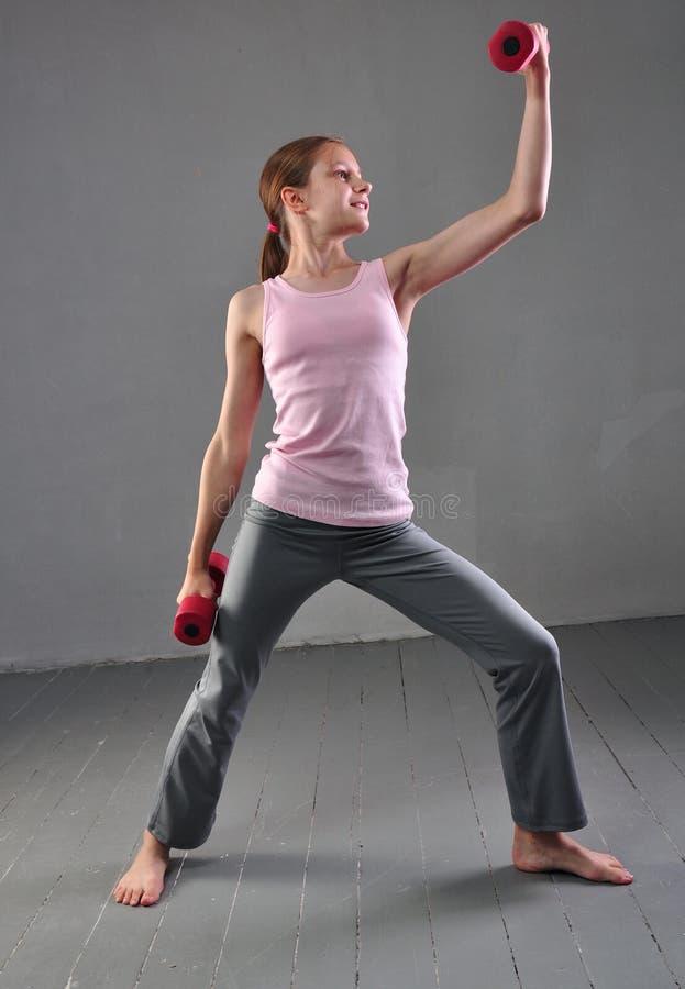 Att se ner tonårs- sportive flicka gör övningar för att framkalla med hantelmuskler på grå bakgrund Sund sport arkivfoton