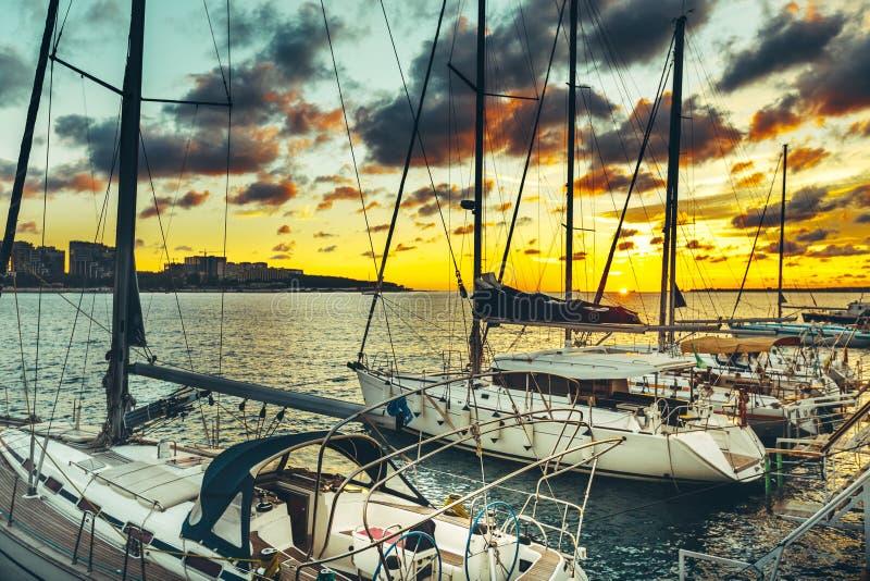 Att segla yachter förtöjde på pir på solnedgången arkivfoto