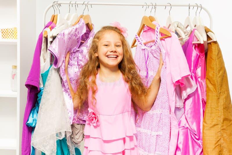 Att skratta flickan står mellan hängare med klänningar royaltyfri fotografi