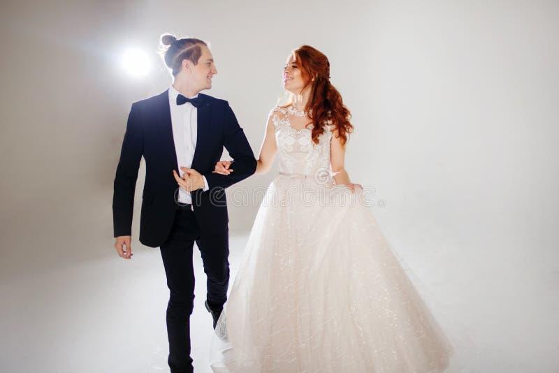 Att skratta och den lyckliga bruden och brudgummen, dansen och hoppet med lycka, att gifta sig royaltyfri foto