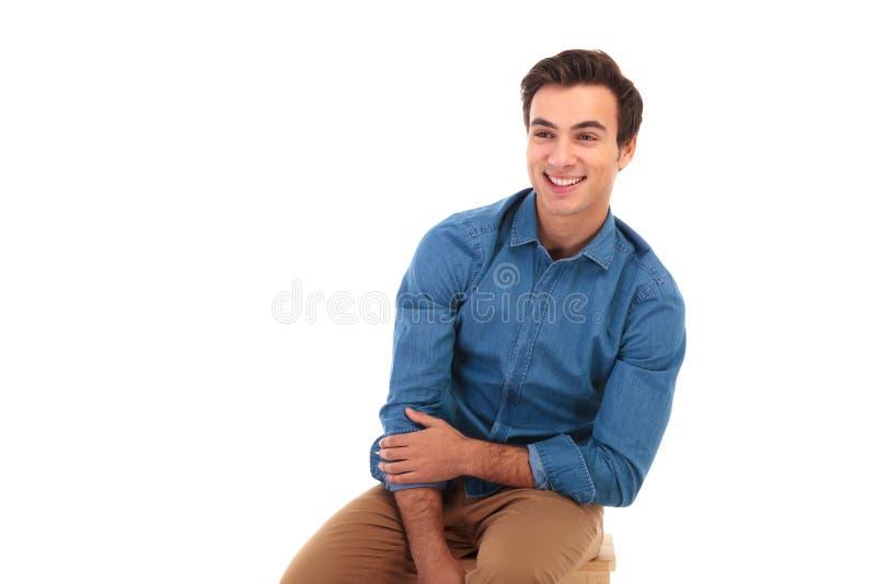 Att skratta ungt tillfälligt mansammanträde på stol ser för att sid arkivbild