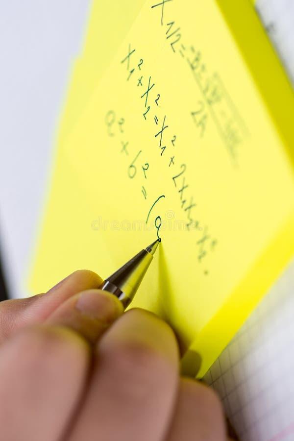 Att skriva på gula klibbiga anmärkningar stänger sig upp arkivfoton