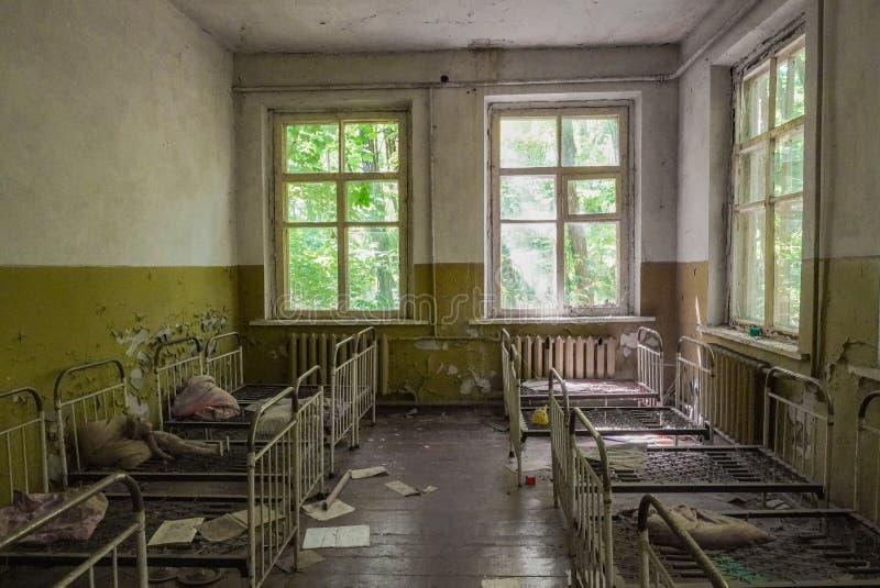 Att smula fördärvar av ett sovrum i en skola i Pripyat, Ukraina nära Tjernobyl som övergavs efter den kärn- olyckan arkivbild