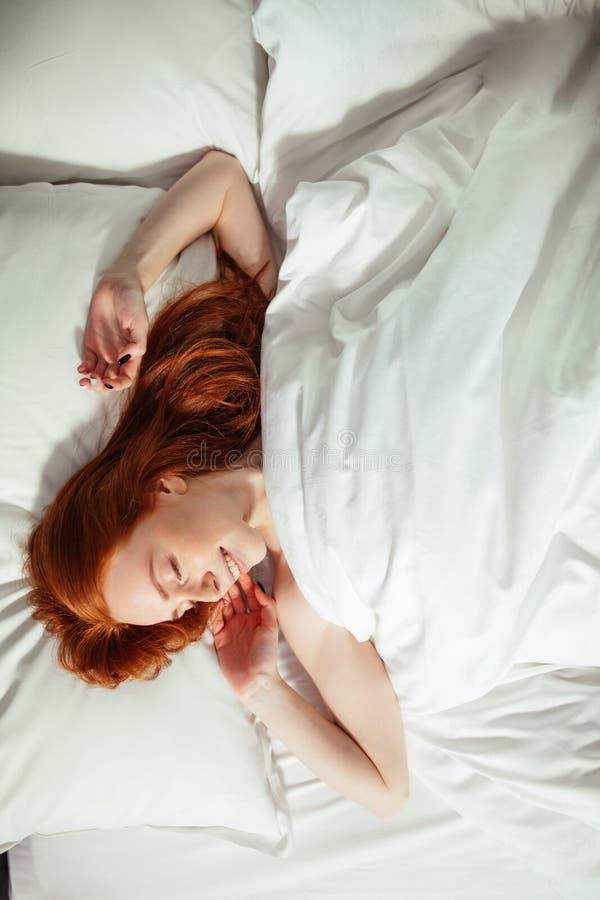 Att sova den unga kvinnan ligger i säng med stängda ögon Top beskådar royaltyfria bilder