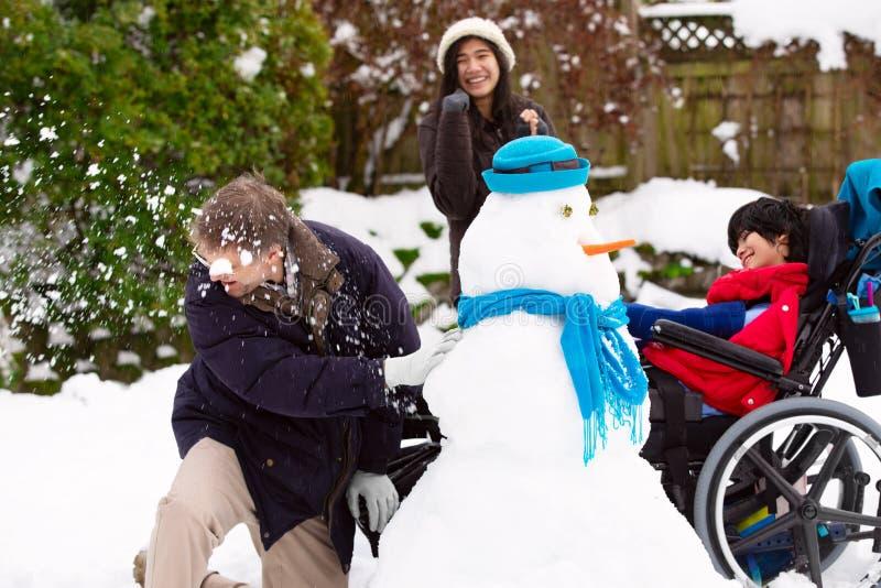 Att spela för fader kastar snöboll kamp med den rörelsehindrade sonen i vinter royaltyfri foto