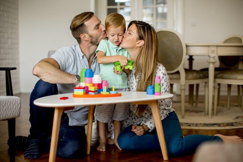 Att spela för pys leker med modern och fadern hemma royaltyfri foto