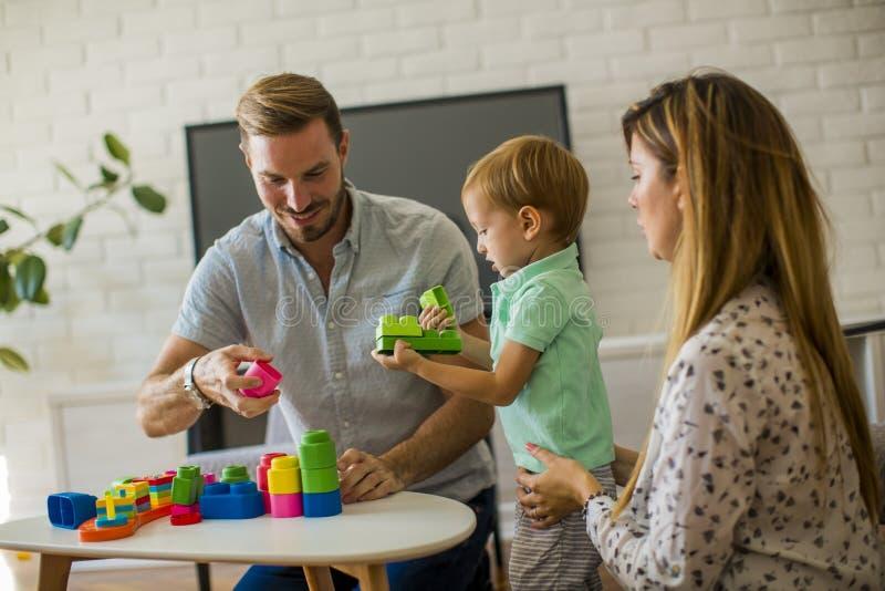 Att spela för pys leker med modern och fadern hemma royaltyfria foton