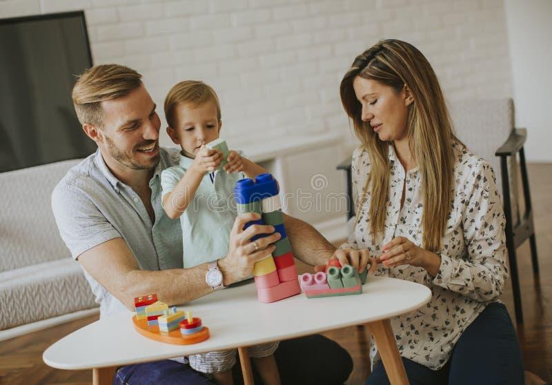Att spela f?r pys leker med modern och fadern hemma royaltyfri fotografi