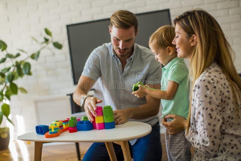 Att spela f?r pys leker med modern och fadern hemma fotografering för bildbyråer