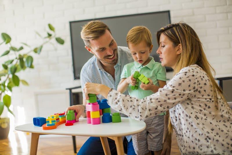 Att spela f?r pys leker med modern och fadern hemma arkivfoto