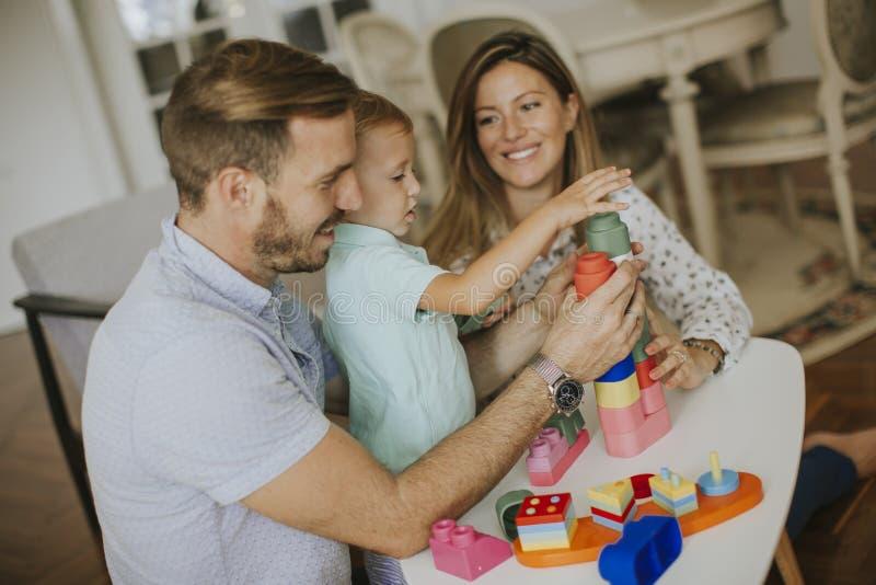 Att spela f?r pys leker med modern och fadern hemma arkivbilder