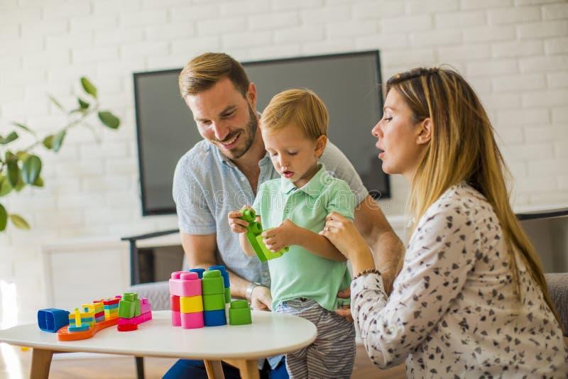 Att spela f?r pys leker med modern och fadern hemma royaltyfria bilder