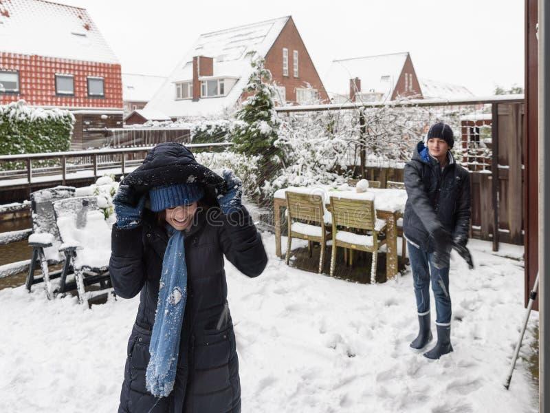 Att spela kastar snöboll i en trädgård royaltyfria foton