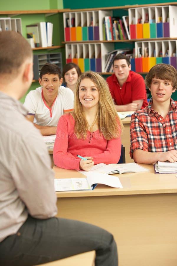 att studera för klassrumdeltagare som är tonårs-, handleder royaltyfria foton