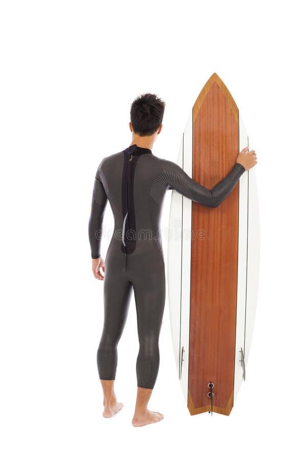 Att surfa mannen bar den våta dräkten och den hållande surfingbrädan royaltyfri foto