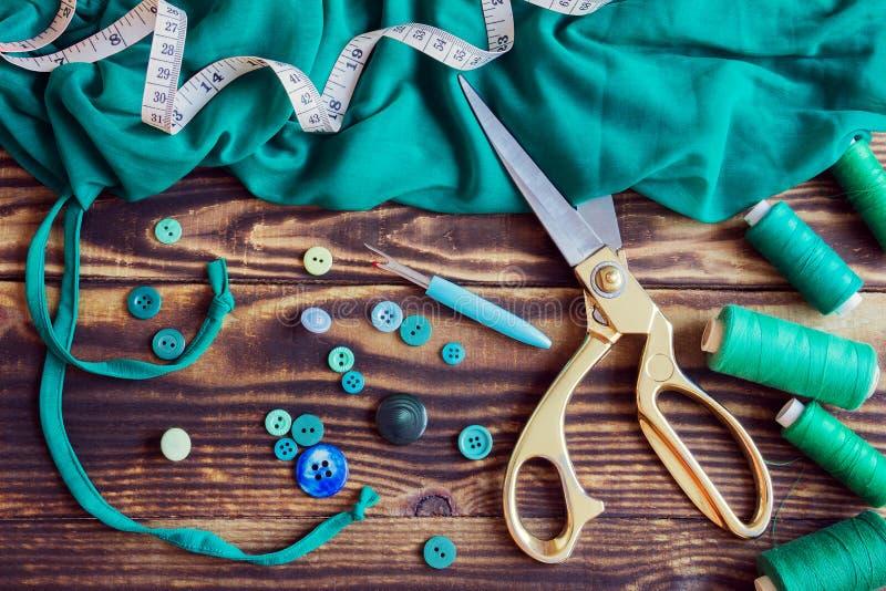 Att sy hjälpmedel, grönt tyg, dragar och knäppas på en träbakgrund fotografering för bildbyråer