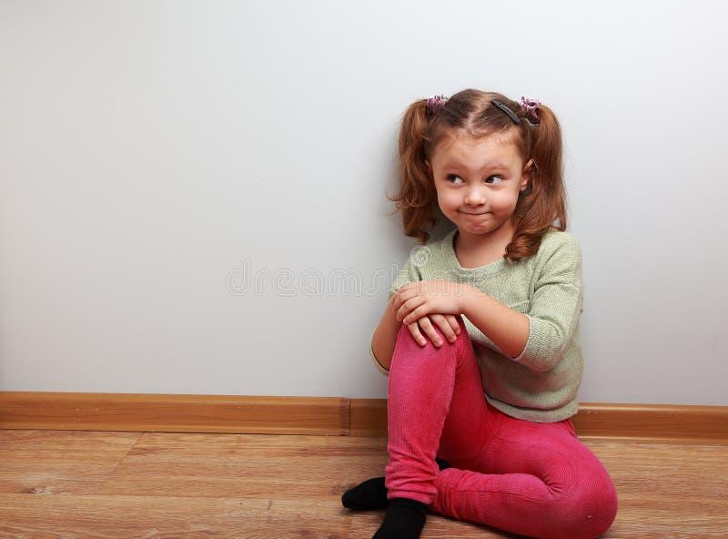 Att tänka blidkar flickasammanträde på golvet med rolig blick arkivfoto