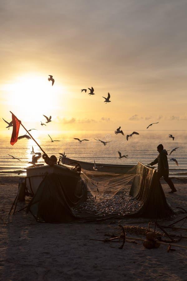 Att tömma för fiskare som är deras, förtjänar på stranden royaltyfri bild