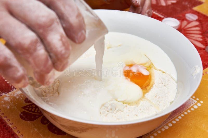 Att tillfoga mjölkar för att bowla med ingredienser för deg arkivfoto