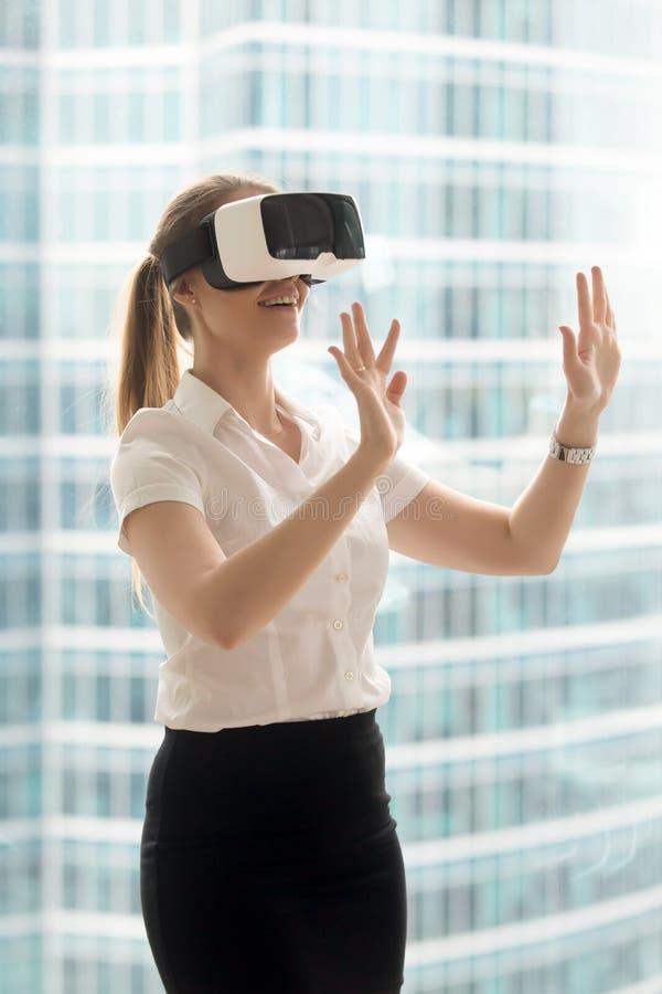 Att tycka om för affärskvinna som är faktiskt, turnerar i VR-hörlurar med mikrofon royaltyfri bild