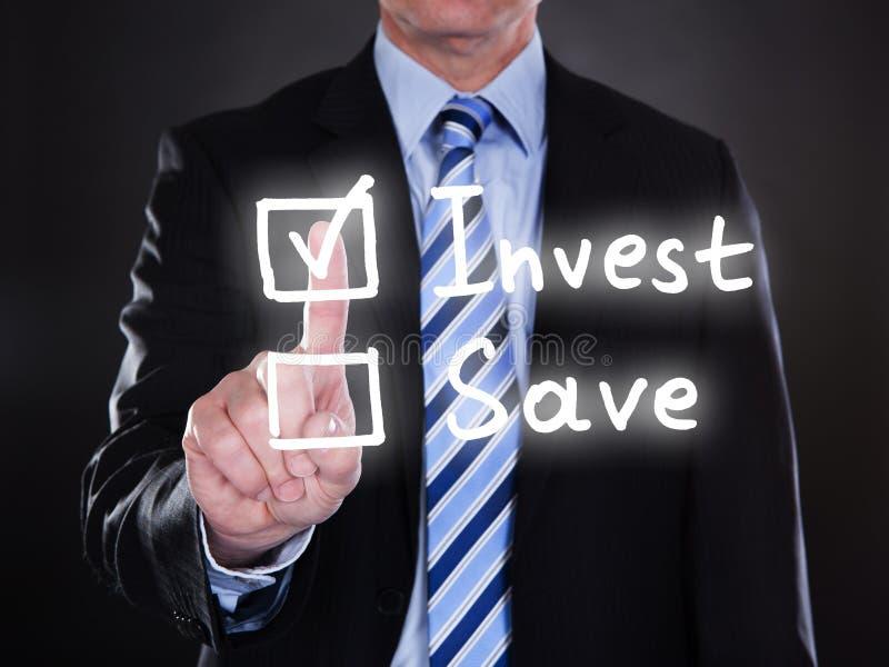 Att välja för affärsman investerar alternativ på skärmen arkivbild