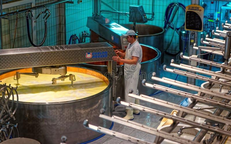 Att värma mjölkar i en kopparkokkärl för att göra en berömd Gruyereost royaltyfria foton