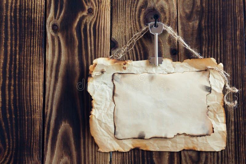 Attaccatura della carta chiave e bruciacchiata su un fondo di legno immagini stock libere da diritti
