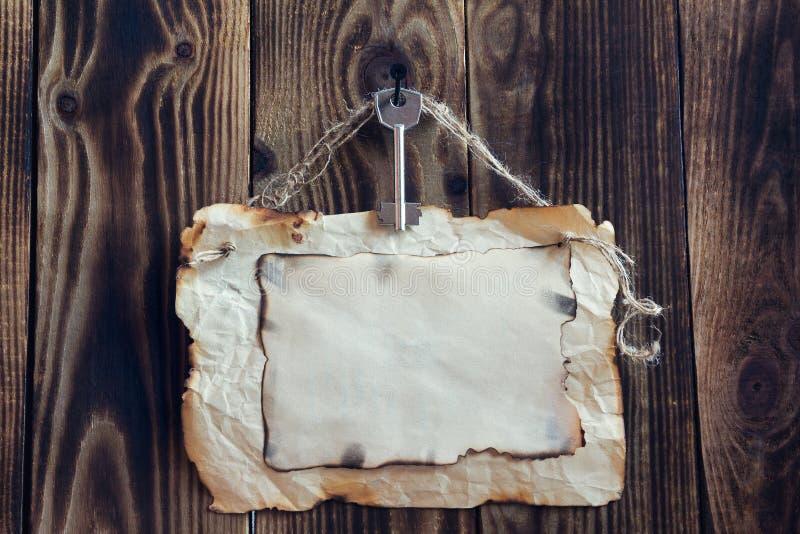 Attaccatura della carta chiave e bruciacchiata su un fondo di legno fotografia stock libera da diritti