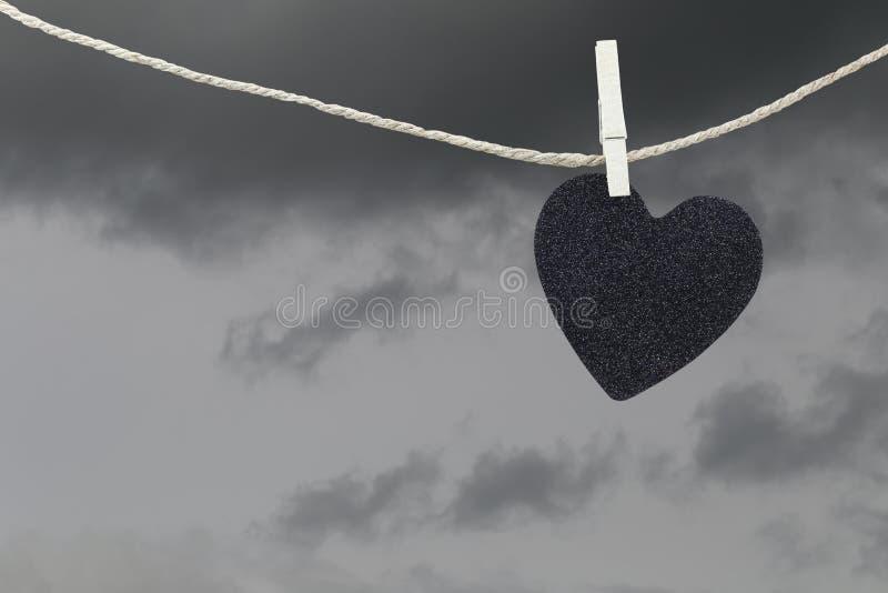 Attaccatura di carta del cuore nero su una corda marrone della canapa sulle sedere delle nuvole di pioggia fotografie stock