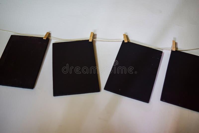 Attaccatura di carta nera del primo piano da rope con le mollette per il bucato su fondo bianco fotografia stock libera da diritti
