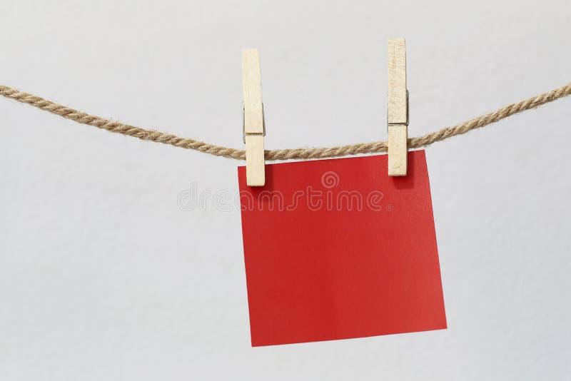 Attaccatura di carta per appunti rossa sulla corda sulla parete bianca fotografia stock