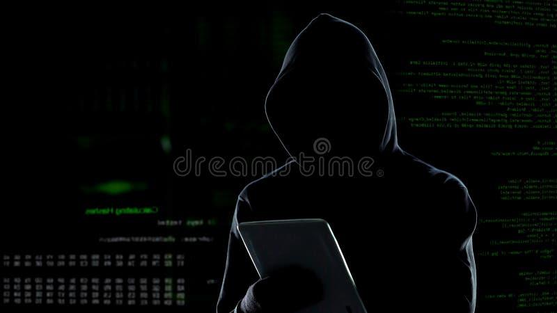 Attacco cyber con il pirata informatico incappucciato irriconoscibile che per mezzo del computer della compressa, cibercrimine immagini stock