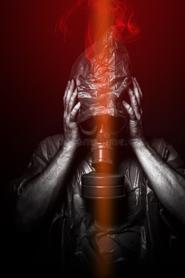 Attacco tossico. Un uomo in una maschera antigas nel fumo. backgro artistico fotografie stock