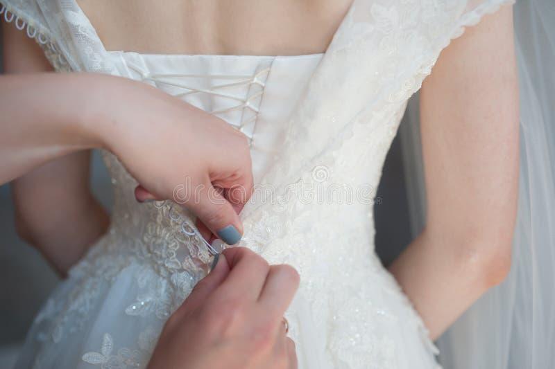 Attachement de la robe, attache de bouton sur la robe du ` s de jeune mariée, honoraires du ` s de jeune mariée, robe de mariage images stock