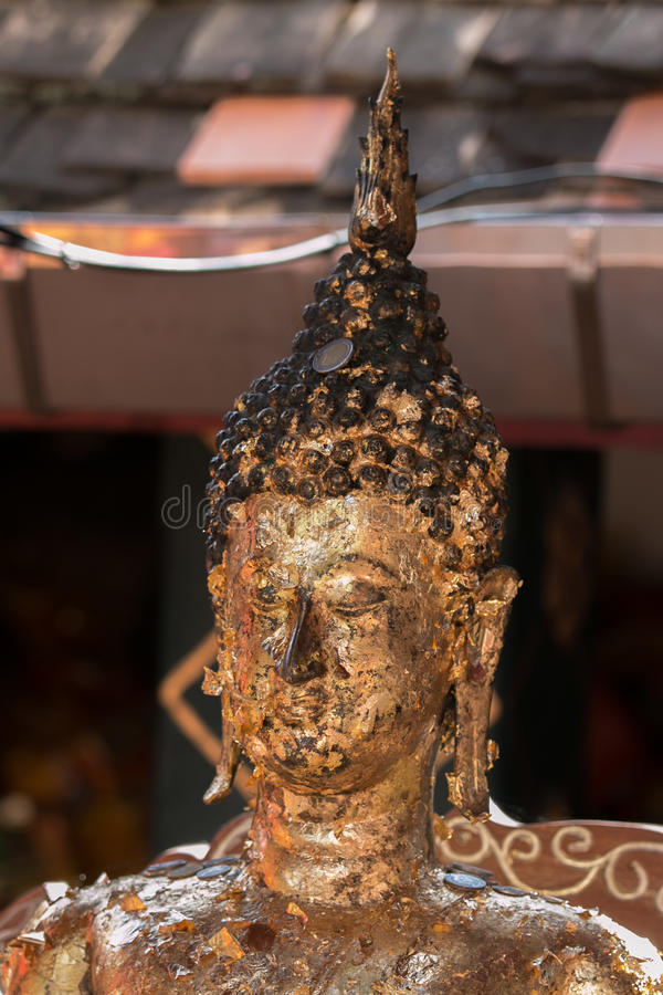 Attaching gold lead to the Buddha statue royalty free stock image