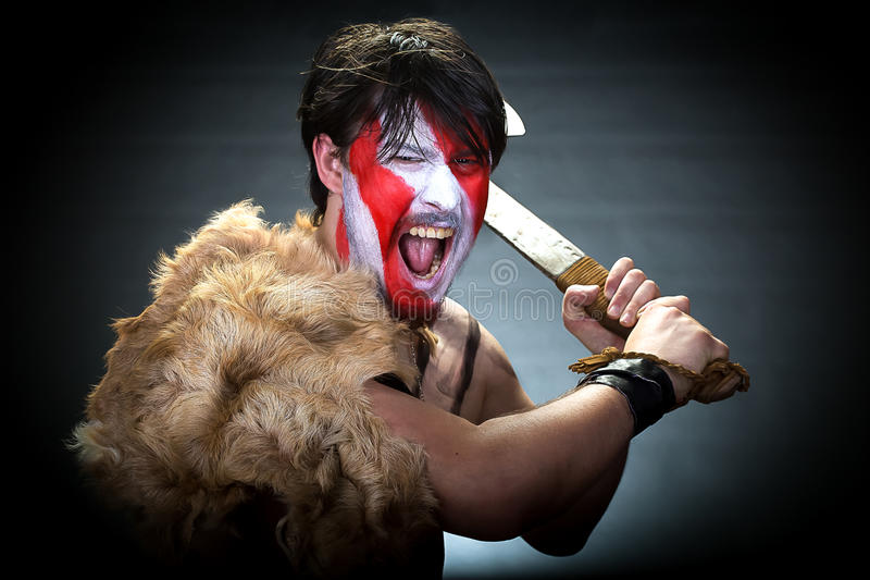 Attaching savage. Portrait of man in war paint, with an ax in his hands, a warrior brandishing an ax furiously screaming, barbarian of ancient times, Viking and stock photography
