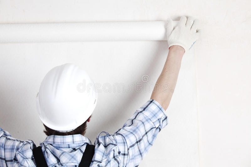 Attaching wallpaper. Worker attaching wallpaper to wall royalty free stock photo