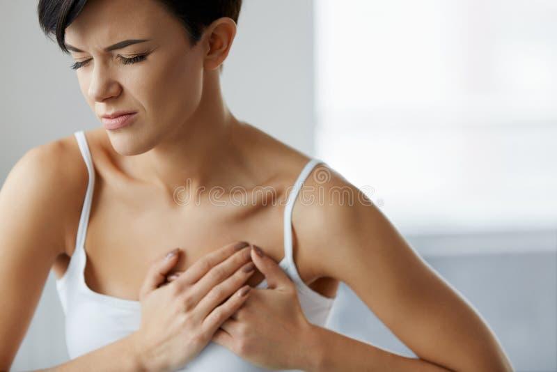attackhjärta håller mannen Härlig kvinnakänsla smärtar i bröstkorghälsovård royaltyfria bilder