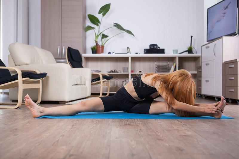 Attactive young woman being flexible during her home training. Home healthy training stock image