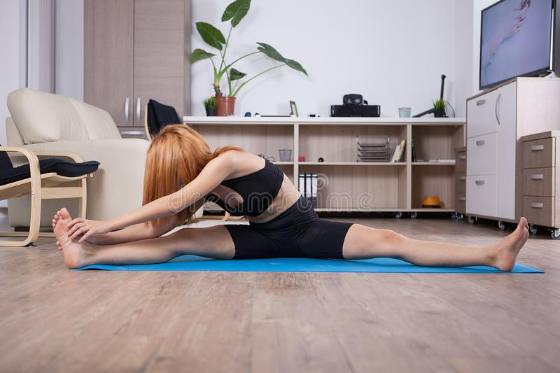 Attactive young woman being flexible during her home training. Home healthy training stock photo